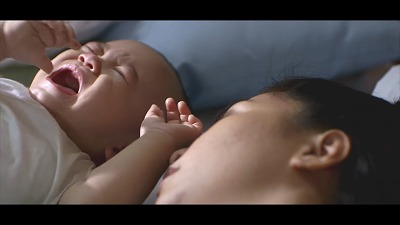 泣く赤ちゃんと寝ている女性